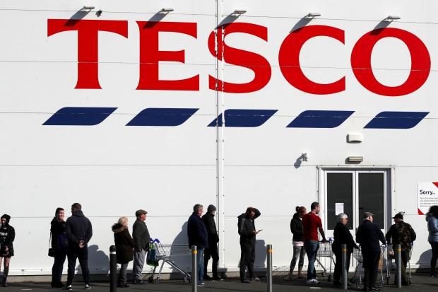Slough Observer: People queue outside a Tesco Extra store in Madeley, Shropshire