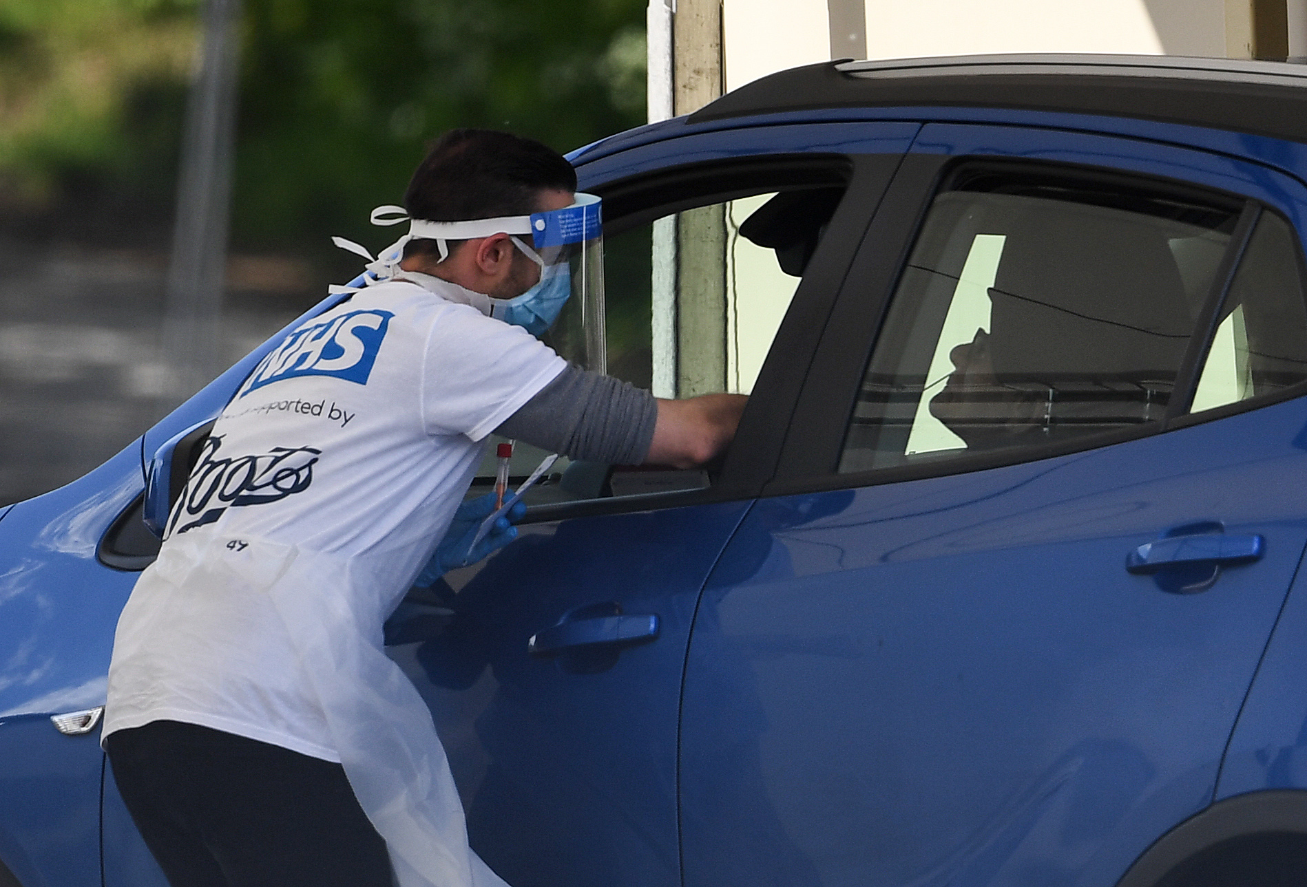 A medical worker takes a swab at a drive-in coronavirus testing facility. PA Photo.,