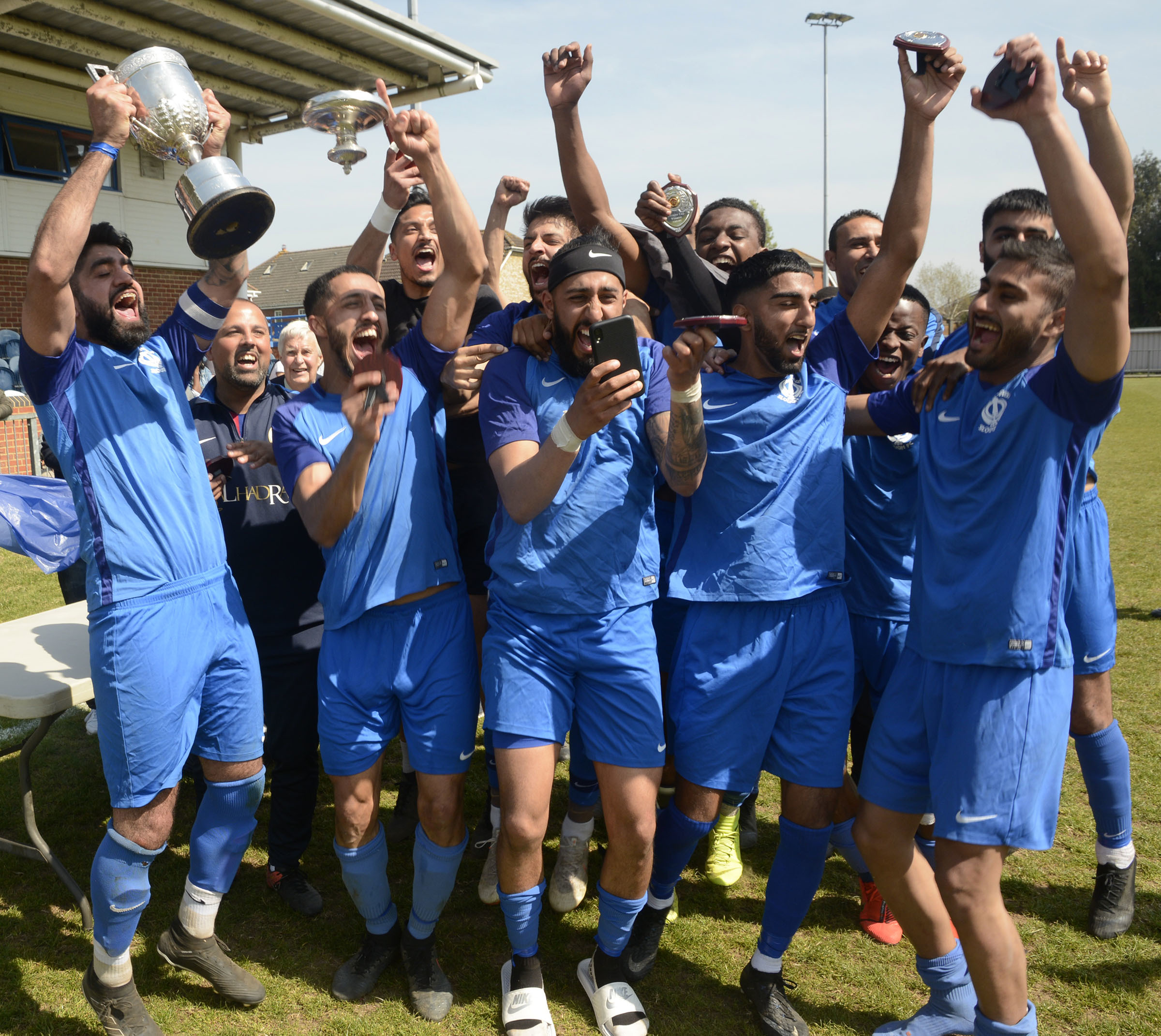 Singh Sabha (blue) celebrate with the Slough Town Challenge Cup after a 2-1 win against Langley (red and blue) in the final at The Gore in Burnham on Good Friday. PHOTOS: Paul Johns. 190458.