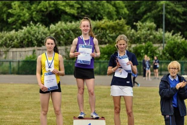 Imogen Wilson, centre, of Maidenhead Athletics Club tops the podium after victory in the 300m in the Berkshire Counties Schools Championships.